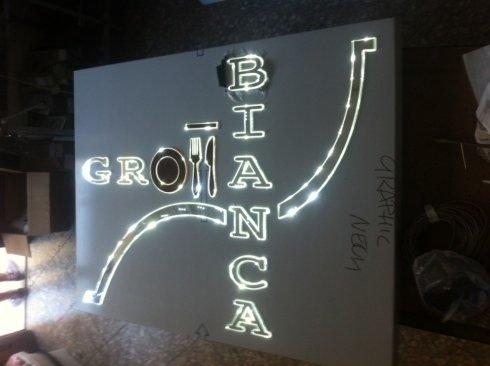 un cartello luminoso  con scritto Grom bianca