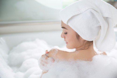 Giovane godendo di un bagno di schiuma