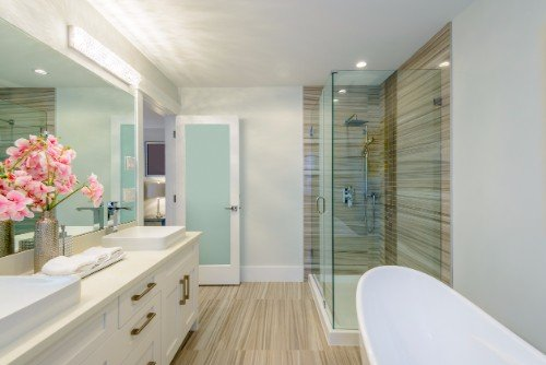 Bagno con pavimento in legno e legno nella parete del box doccia