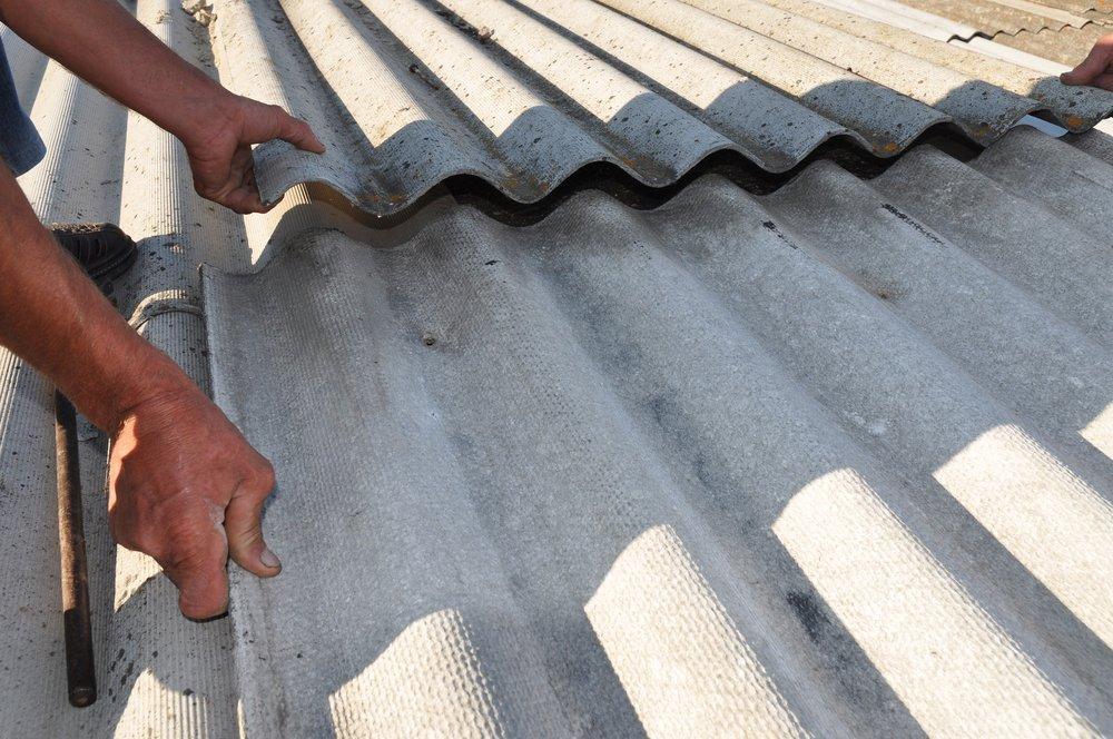 operaio mentre installa amianto su un tetto di una casa