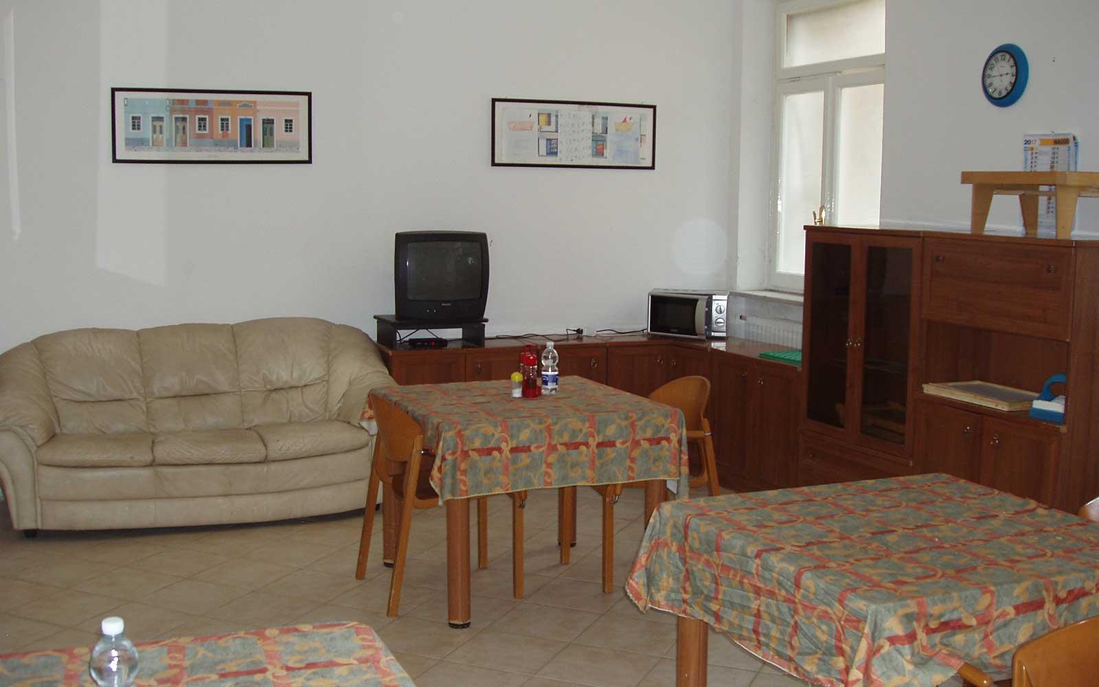 un divano in pelle beige e dei tavoli con delle sedie