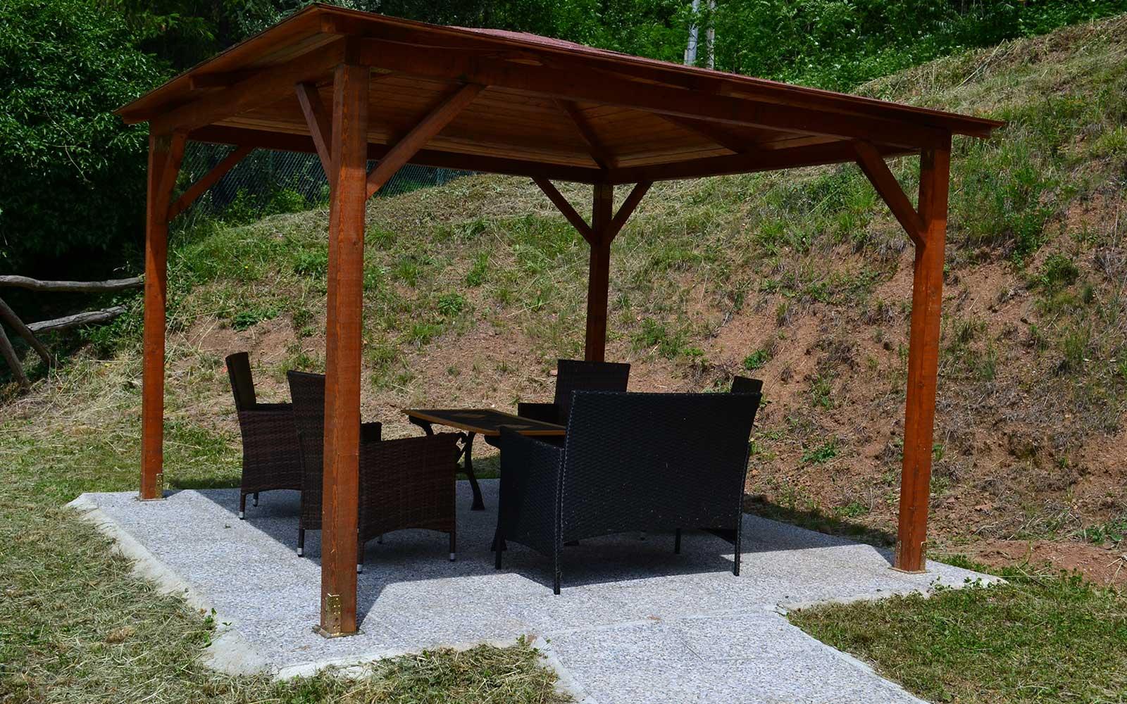 un gazebo in legno con delle sedie e un tavolo sotto