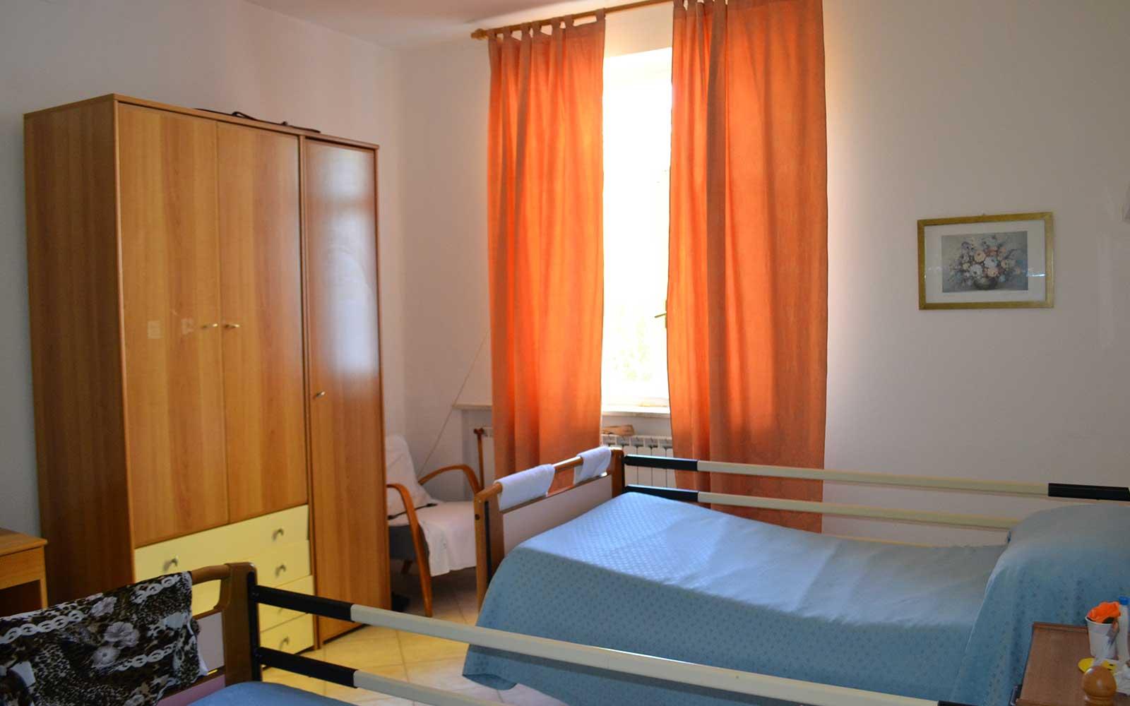 una camera con due letti ospedalieri e un armadio in legno