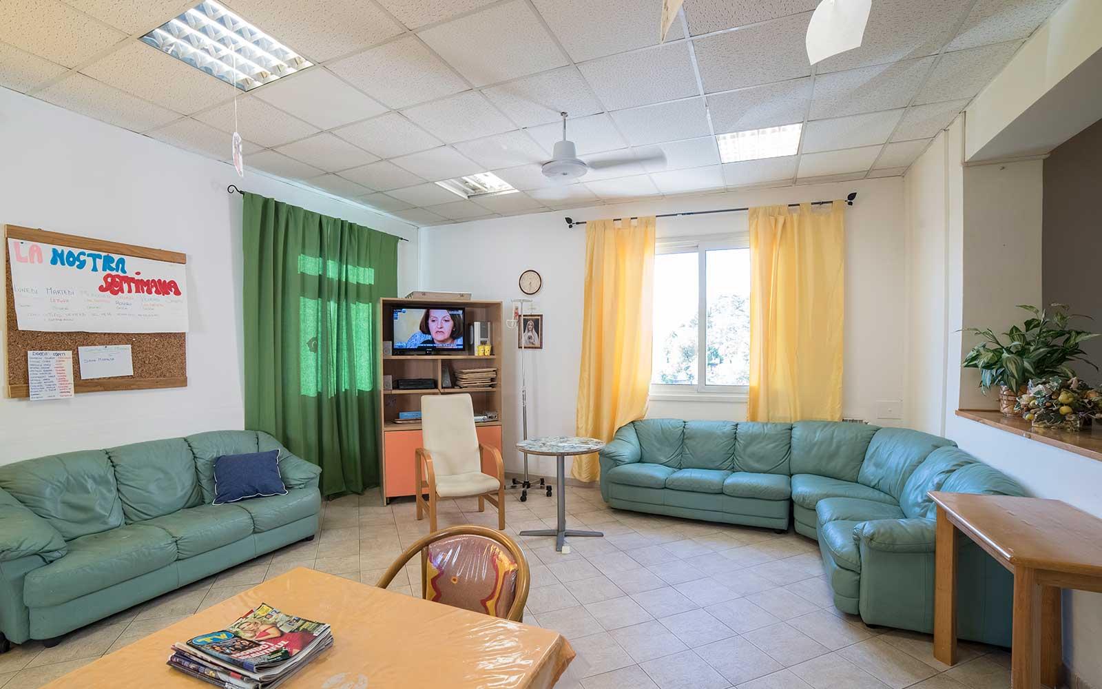 una sala con due divani verdi, una TV è un tavolo con una sedia