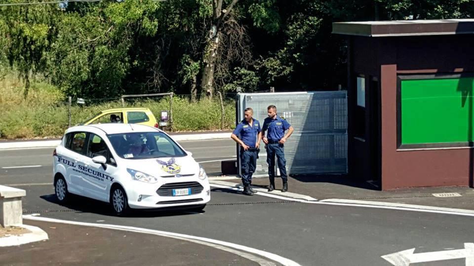 due uomini della sicurezza di fianco auto