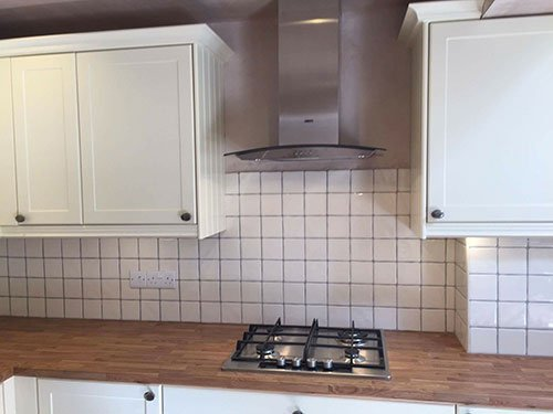 tilled kitchen with white and woode furniture
