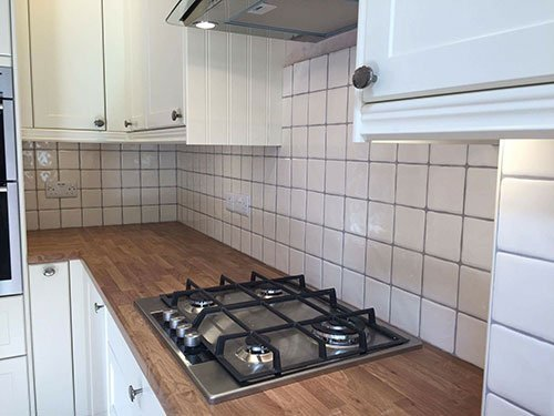 tilled kitchen with wooden furniture