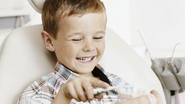 Happy kid is brushing dummy teeth