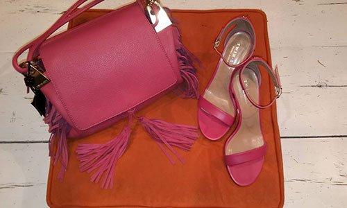 Una borsa di pelle rosa con frangetta e sandali da donna di pelle rosa appoggiati su uno sfondo arancione