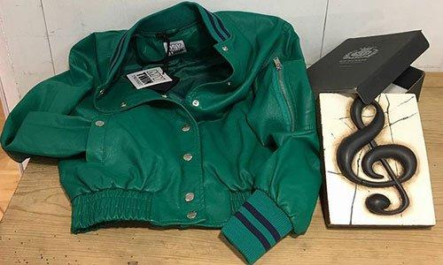 Una giacca in pelle verde esposta su una mensola in legno e un pannello con una chiave di violino nera disegnata