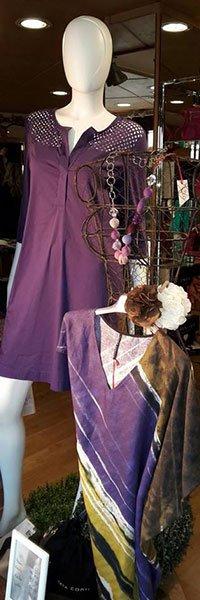 Un manichino con un abito di color viola con maniche lunghe, un appendino con collana e un altro abito di color viola