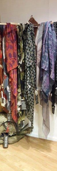 vista di alcune sciarpe di seta di colori diversi appese a un appendiabiti
