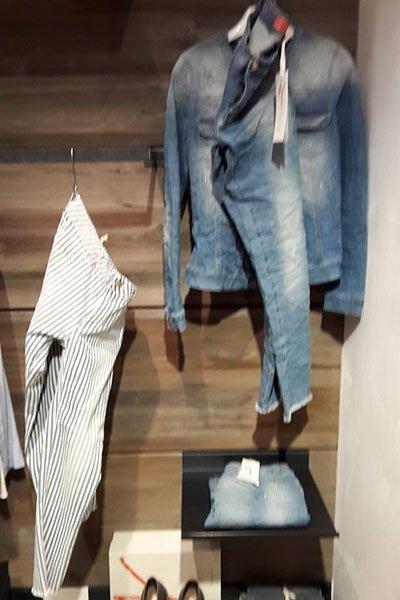 un giubbotto di jeans e dei pantaloni appesi a un ometto e di fianco dei pantaloni bianchi a righe nere fini