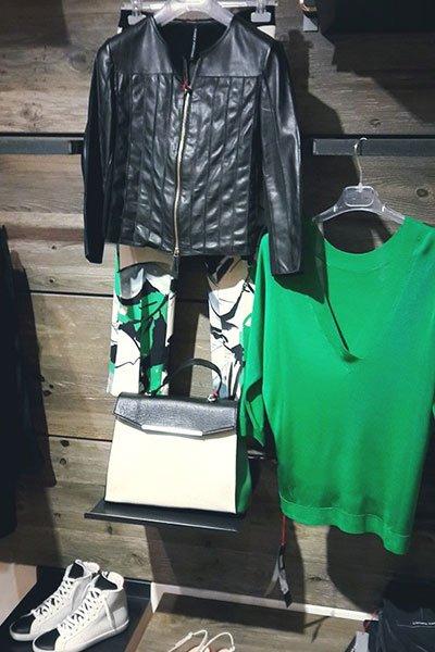un giubbotto di pelle nero, un maglione verde con collo a v, una borsa bianca e nera e un paio di scarpe da tennis bianche