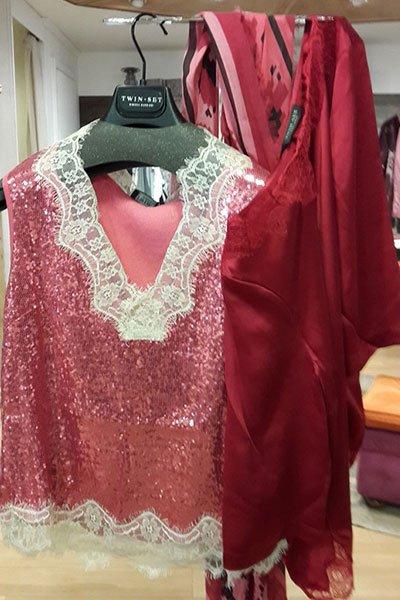 una camicetta trasparente rosa con colletto in pizzo bianco e accanto altri vestiti di color rosso appesi