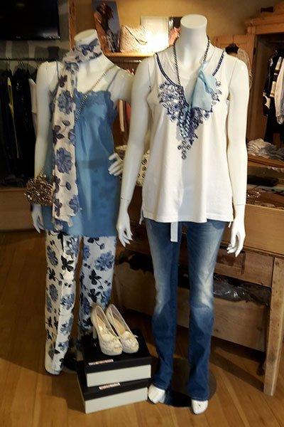 due manichini, uno che indossa un top azzurro con una sciarpa bianca a fiori blu e dei pantaloni bianchi a fiori blu e neri e l'altro un top bianco con un disegno blu e dei jeans