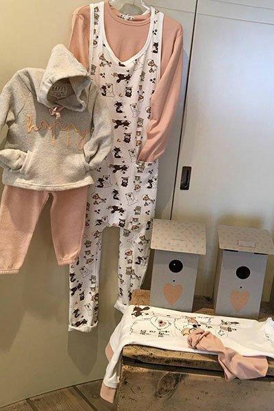 Pigiami: un appendino con felpa grigia e pantaloni rosa per bimbi, un altro appendino con una tuta con disegni di topolino e maglia rosa