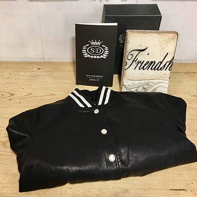 Una giacca di pelle nera con bottoni bianchi e colletto a righe bianche, appoggiato su uno sfondo di legno e uno broschuro con scritto SD