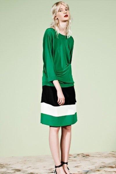 Una donna in posa per una foto con una camicia verde e una gonna di colore verde,bianco,nero e dei sandali neri