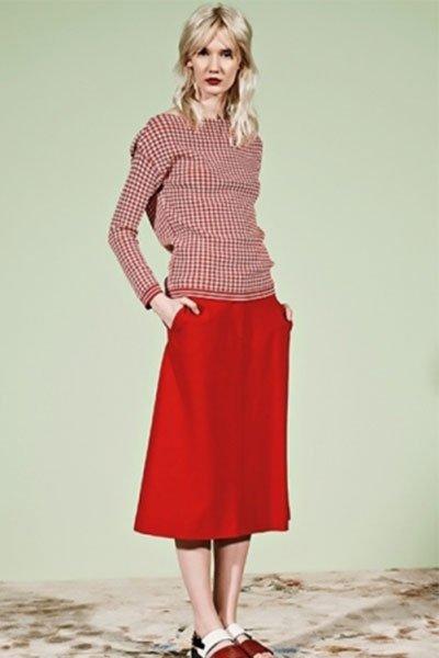Una modella con capelli biondi che indossa una gonna di color rosso e una camicia a scacchi bianchi e rossi con maniche lunghe