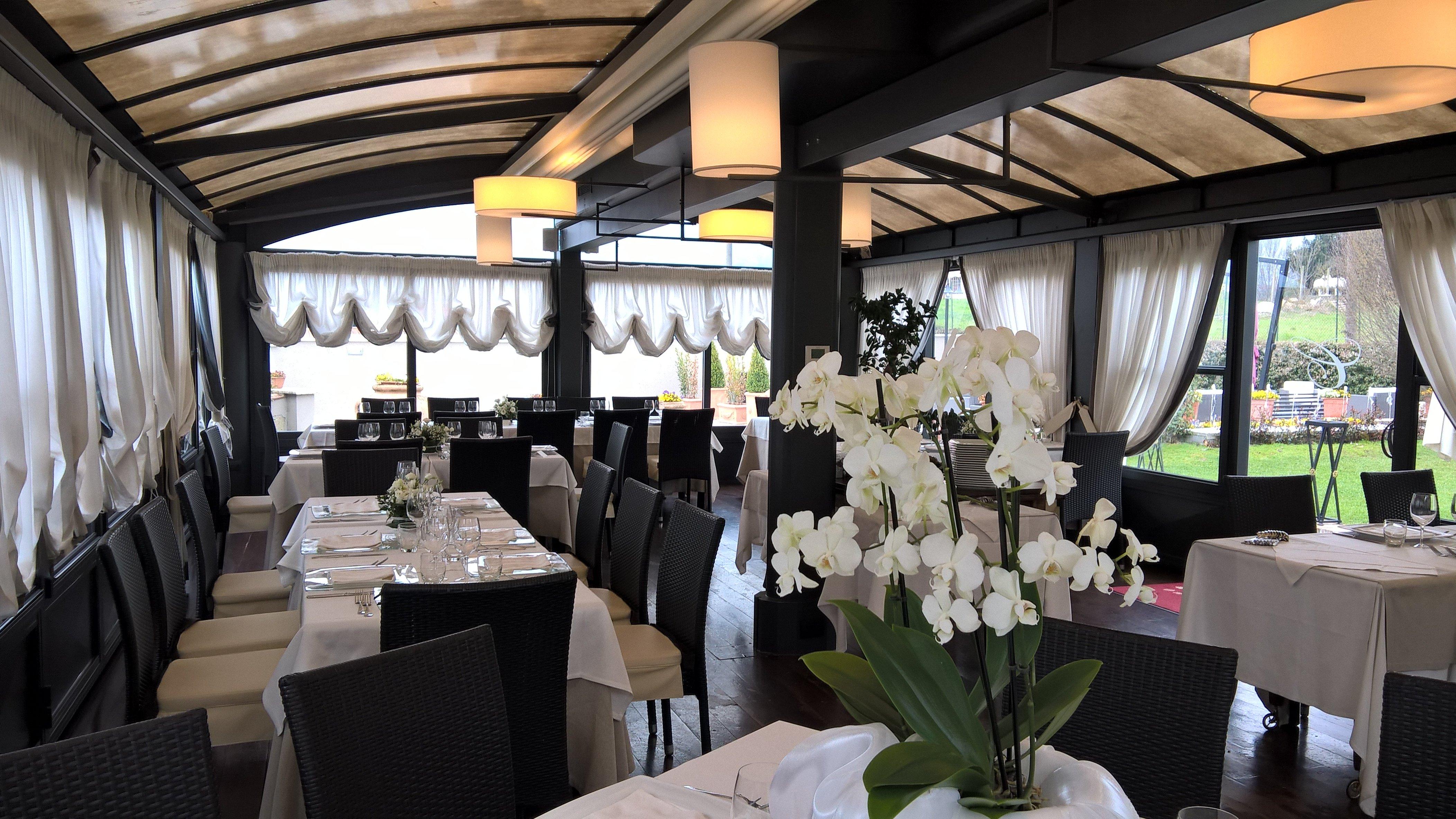 dei tavoli apparecchiati e decorazione con dei fiori