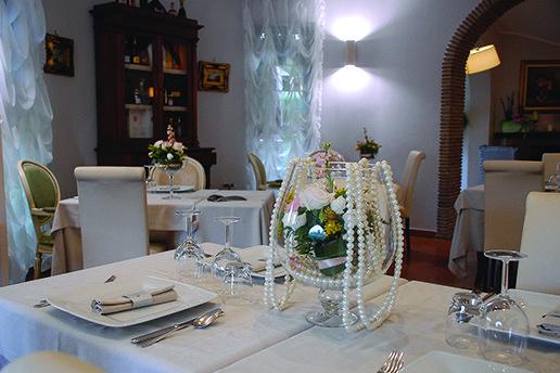 un tavolo apparecchiato e al centro un vaso con delle rose e perle