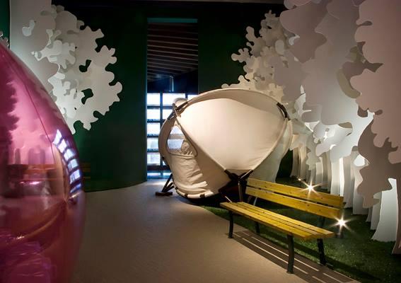stanza con una panchina, prato finto con alberi di cartone di color bianco, un amaca moderna da giardino e sulla sinistra si intravede una palla rosa