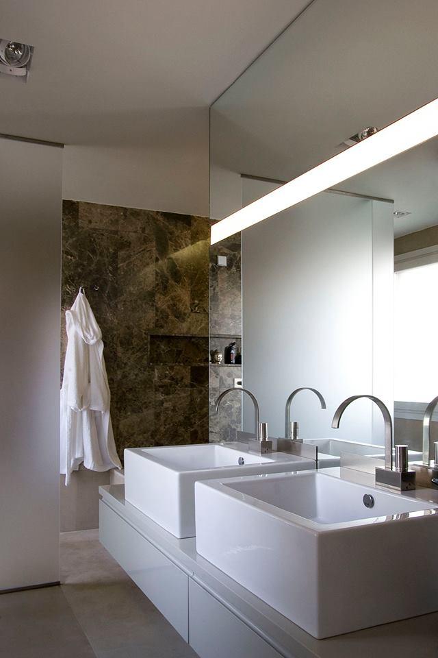 bagno moderno con vista di due lavabi a forma quadrata separati, sulla destra uno specchio e di fronte un accappatoio bianco appeso