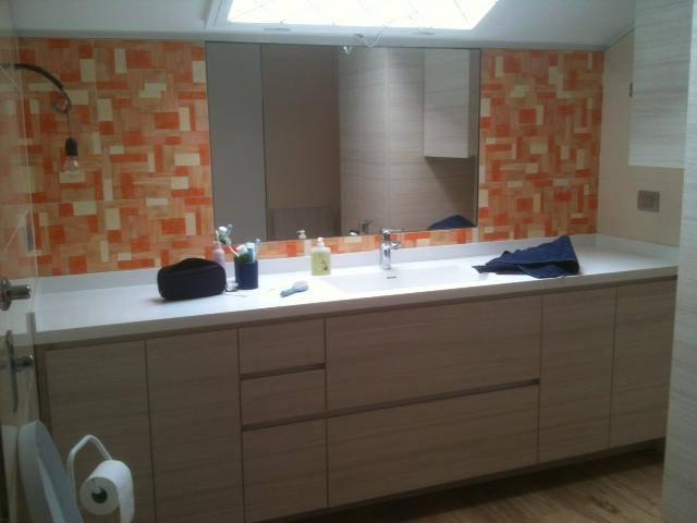 bagno con piastrelle arancioni, specchiera, lavabo centrale con accanto delle trousse e sotto un armadio di color beige