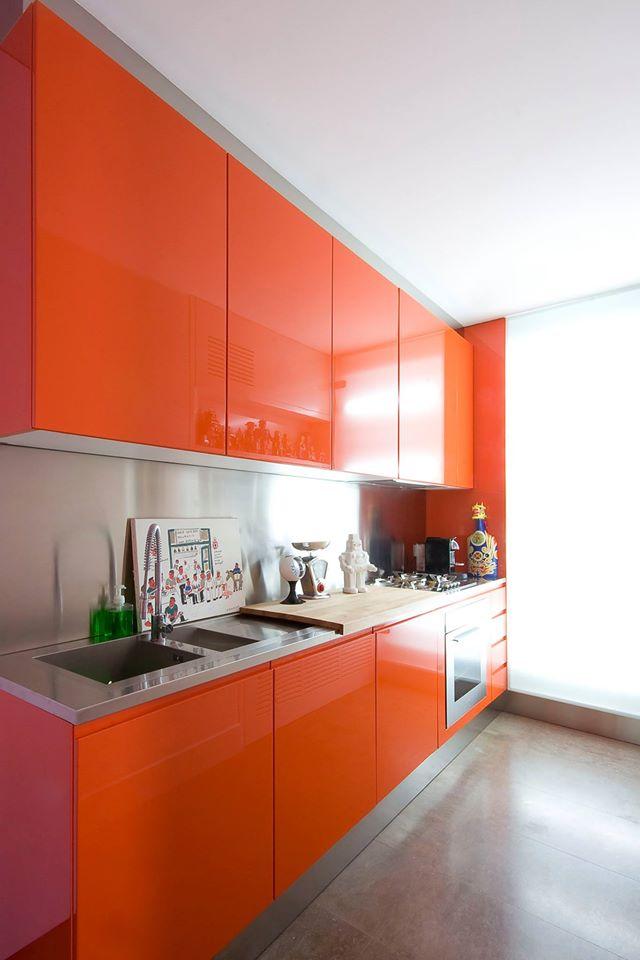 cucina moderna di color arancione vista lateralmente con tagliere e oggetti di porcellana sul pianale, forno in acciaio in basso e sulla sinistra il lavandino