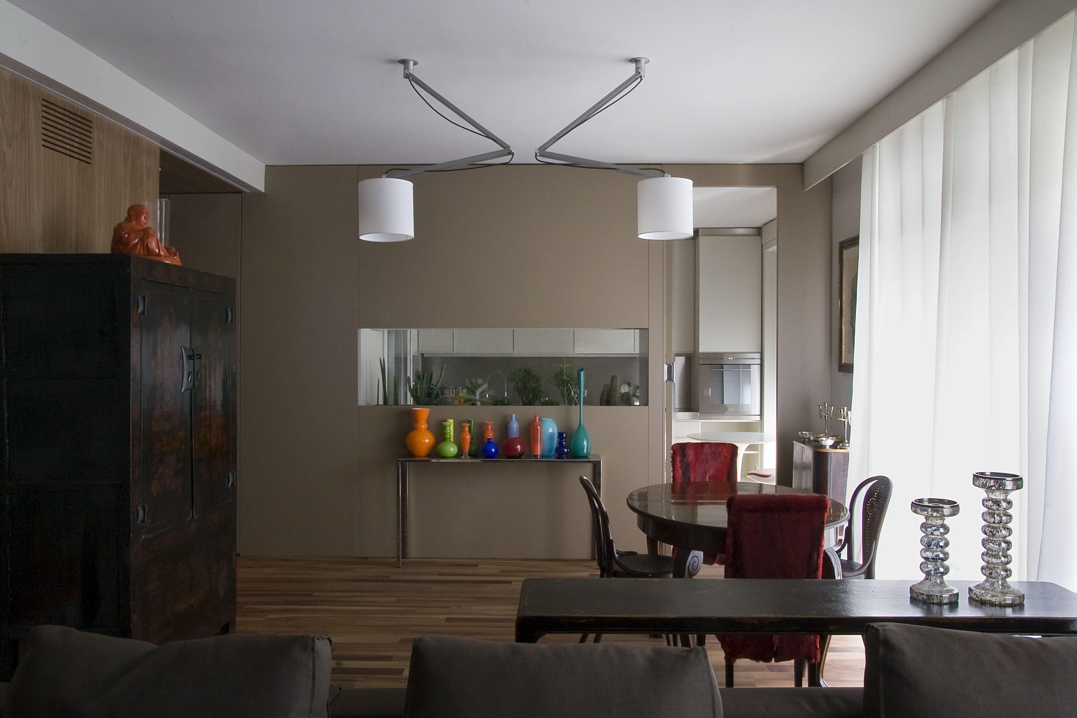stanza con finestra aperta,un calorifero, scrivania con sotto una cassettiera bianca e sulla destra dei vestiti piegati