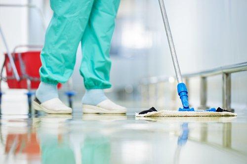 Operatrice pulisce un pavimento con uno spazzolone