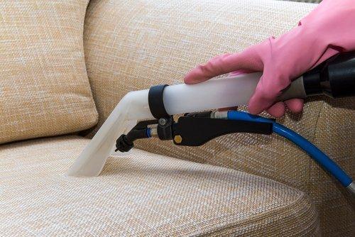 Primo piano di mano che usa aspirapolvere su un divano