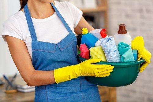 Addetta alle pulizie regge un secchio di prodotti detergentio