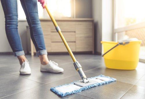 Donna lava pavimento con uno spazzolone