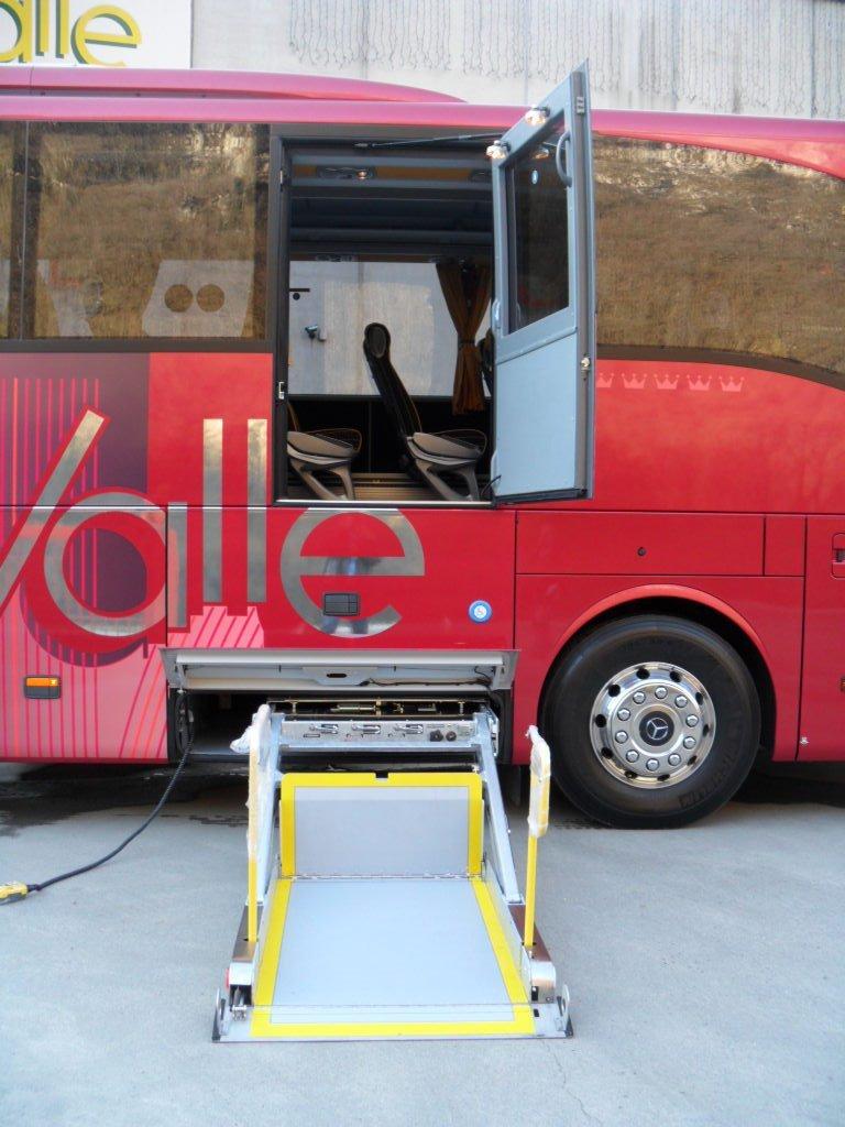 una rampa per portatori di handicap vicino a un pullman rosso