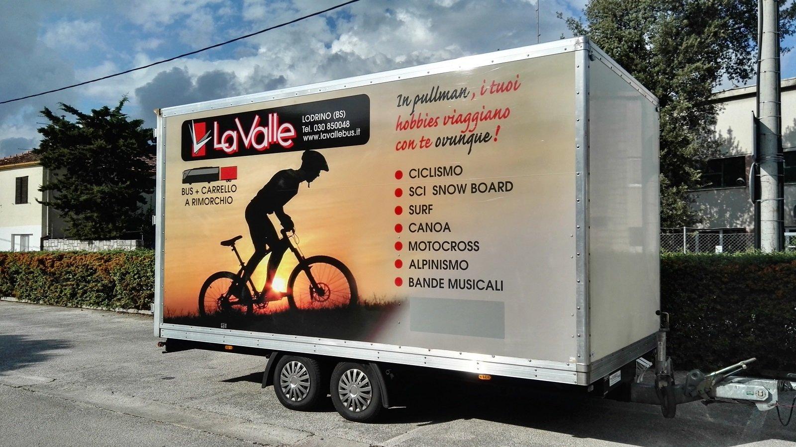 un rimorchio sopra un carrello con l'immagine di un ciclista che pedala al tramonto