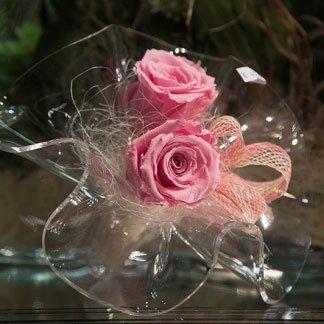 un vaso di cristallo a forma di un fiore con delle rose di color rosa