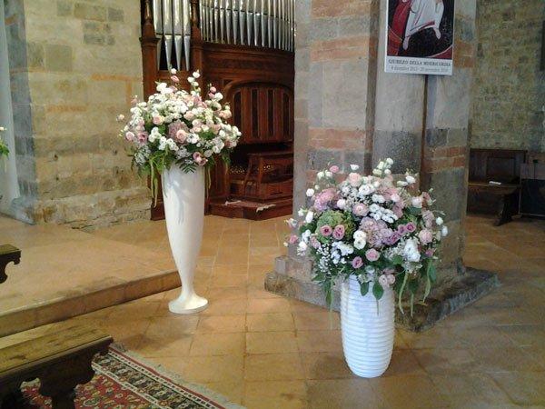 Due vasi di color bianco con delle roselline di color bianco e lilla