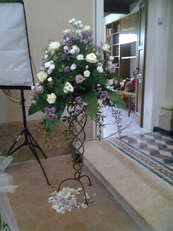 un vaso di ferro con delle roselline di color bianco e lilla