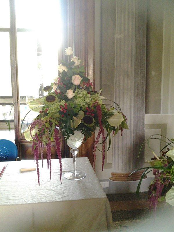 un vaso di cristallo con una composizione di fiori di color verde e delle rose di color bianco