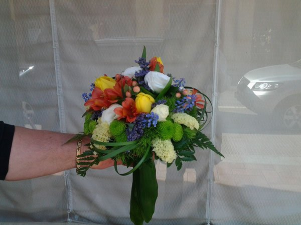 una mano con un bouquet di fiori di color verde, giallo ,bianco, arancione e blu