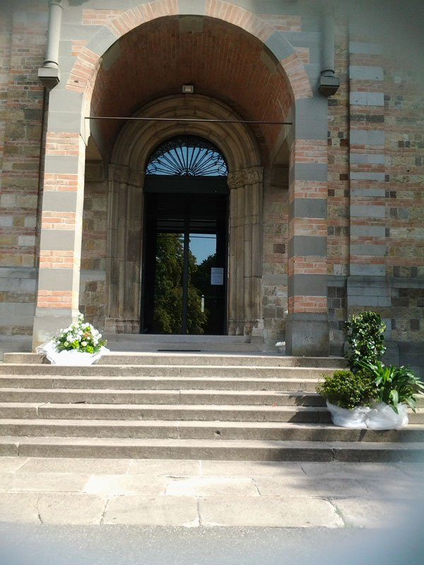 vasi di piante e un bouquet di fiori davanti a una chiesa