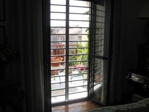 Porta- finestra con tende nere e grata di protezione