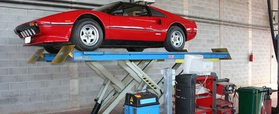 macchina rossa sollevata su un ponte elevatore