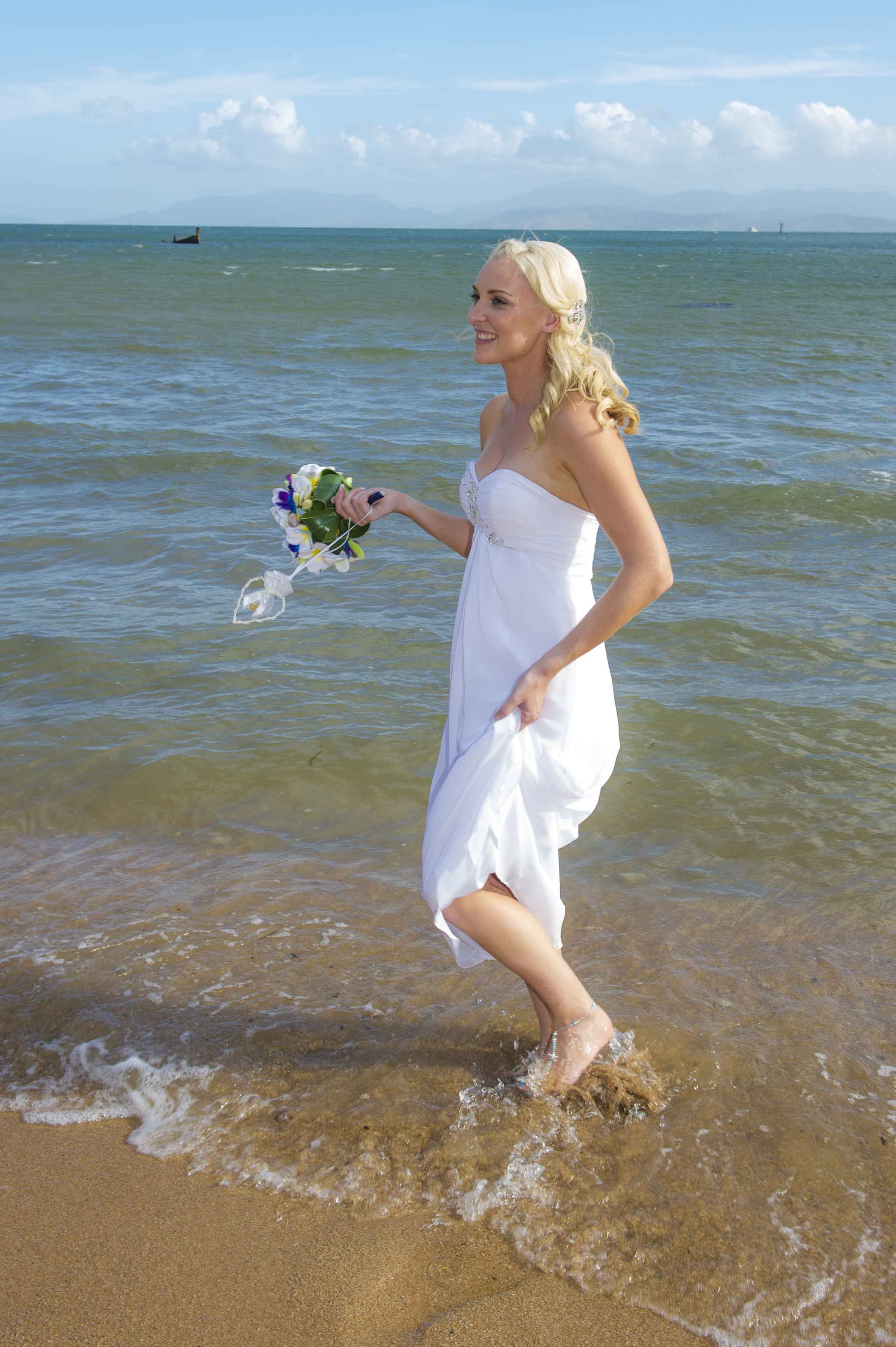 Bride strolling with bouquet of flowers in beach