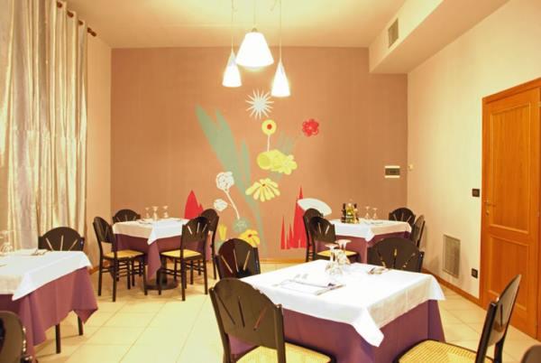 Una delle Camere del ristorante con una delle pareti piena di fiori giganti rosse e gialle,piante verdi e un sole bianco