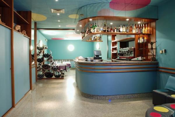 Originale ricezione del ristorante dipinta nel blu turchese, con originali fusti senza coperchi che servono di portabottiglie