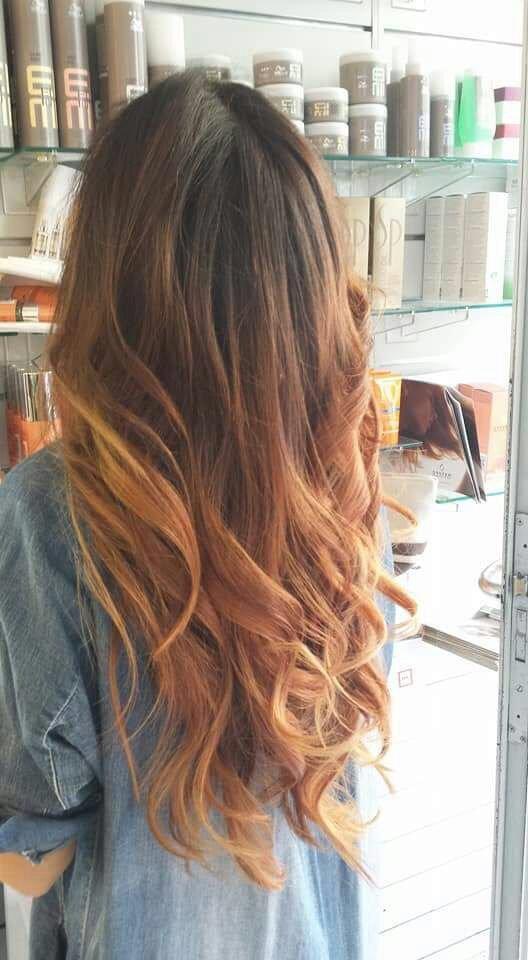 una ragazza con capelli lunghi e mossi color castano e delle  meches bionde