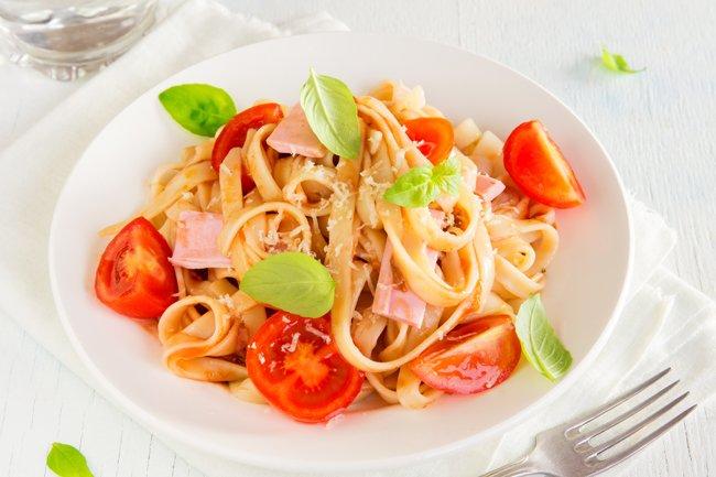piatto di pasta lunga con pomodoro prosciutto e basilico